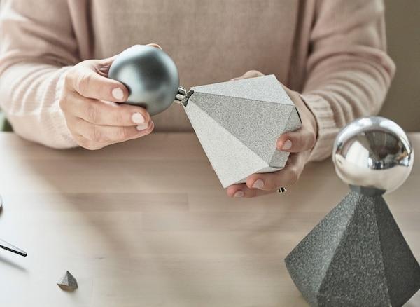 Grijze en zilverkleurige kerstballen worden met hun kroontje in de bovenkant van diamantvormige kartonnen geschenkdoosjes geplaatst.