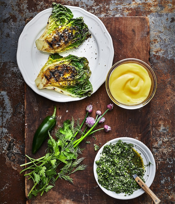 Grilled lettuce and herbs, accompanied by an golden yellow dip sauce and gremolata made with IKEA SMAKRIK rapeseed oil.