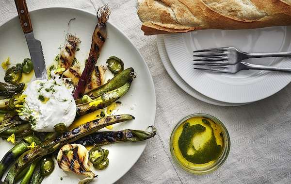 Grilled vegetables, oil and bread on white plates.