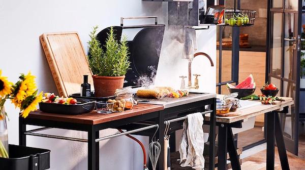 Griller mit Essen im Garten, daneben eine Rosmarinpflanze im Topf