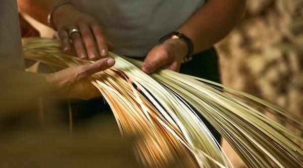 Groene en gele bamboe strengen in de handen van twee mensen