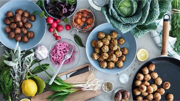 GRÖNSAKSBULLAR veggie balls, KÖTTBULLAR meatballs and ALLEMANSRÄTTEN chicken balls on three separate plates surrounded by a variety of vegetables.