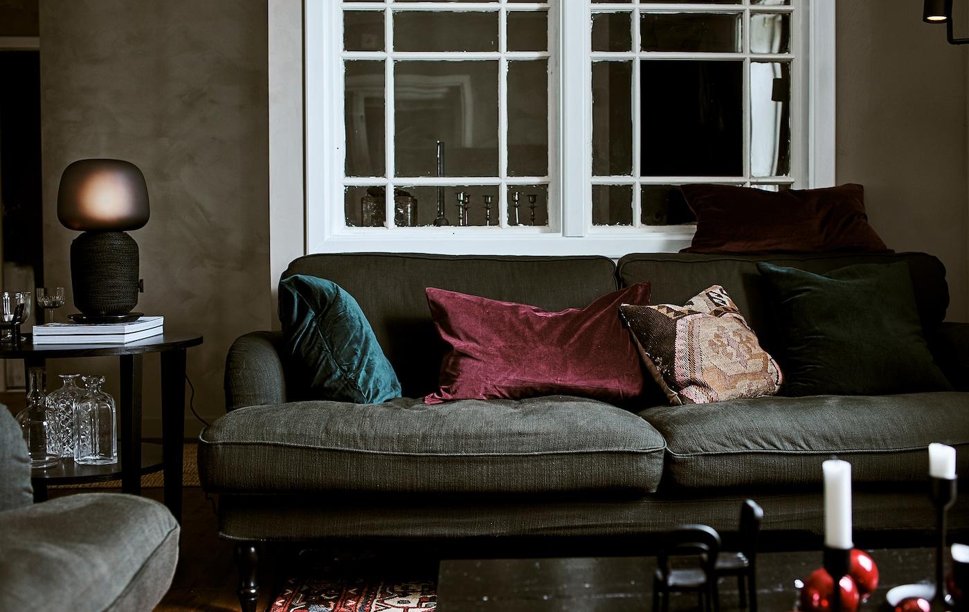 Grønn sofa med puter i grønn og rød fløyel i ei stue med et indre vindu, bord med bordlampe og et persisk teppe.