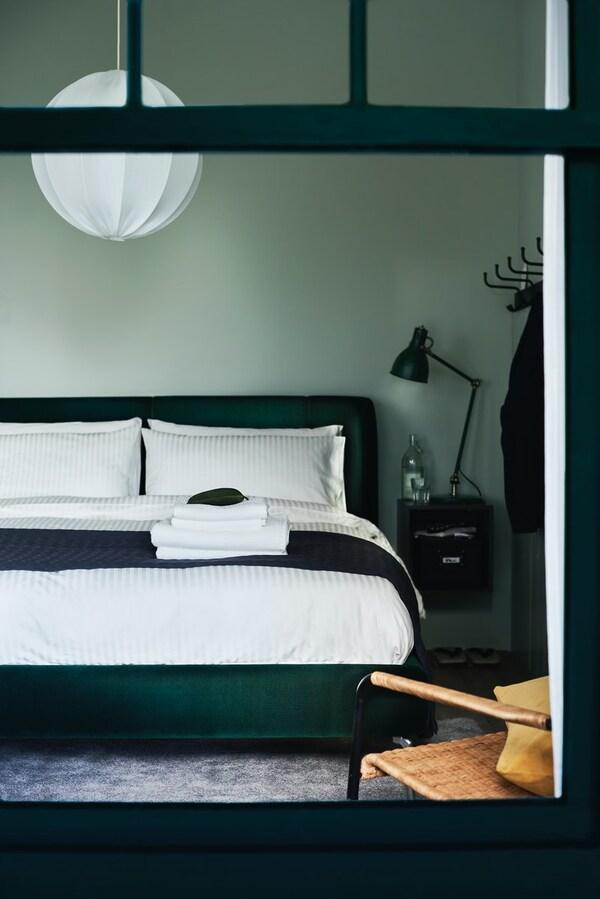 Grønt soverom med mørkegrønn polstret seng redd opp med hvitt sengetøy. På et nattbord er det ei svart arbeidslampe.