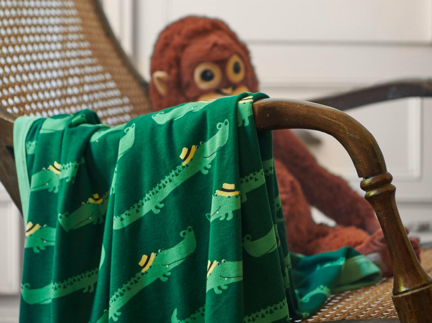 Gros plan de la couverture RÖRANDE avec des crocodiles sympathiques rampant sur un fond vert. La couverture est placée sur une chaise en osier.