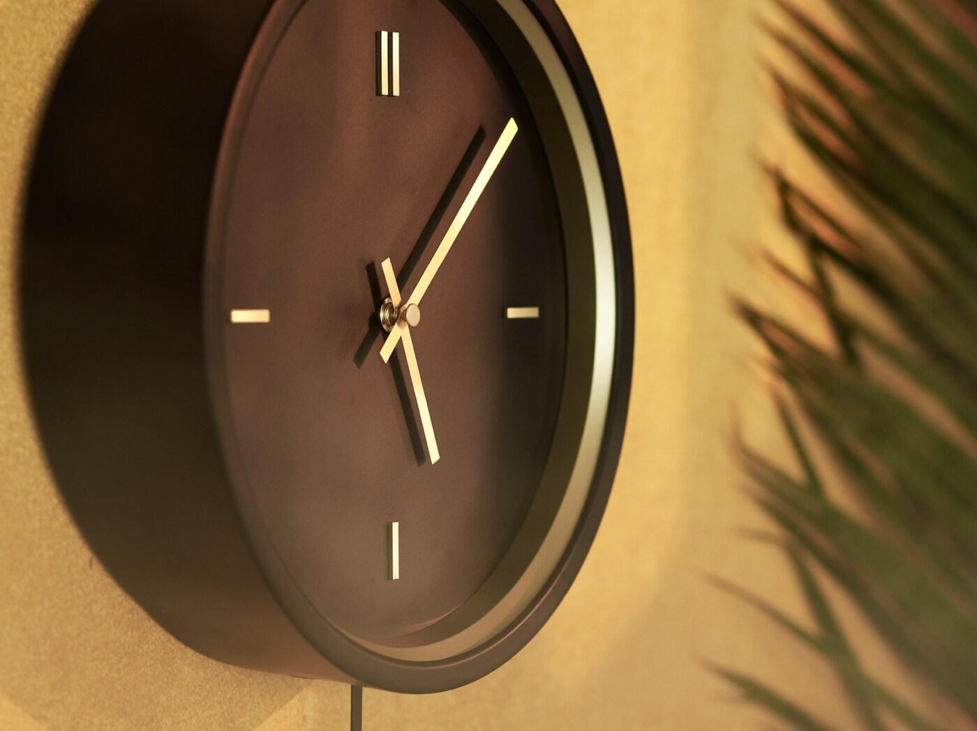 Gros plan de l'horloge murale noire STURSK avec des détails et des aiguilles dorés, accrochée sur un mur brun doré.