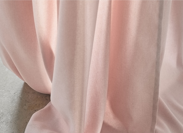 Gros plan du tissu d'un rideau rose.