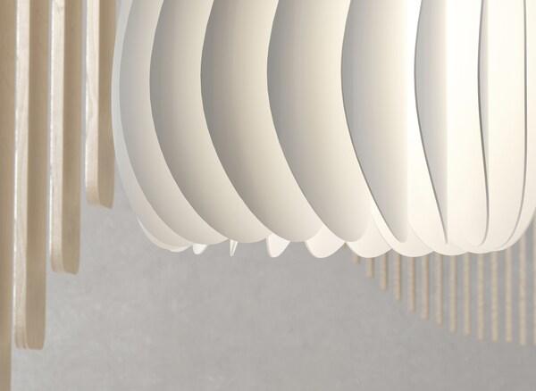 Gros plan d'un abat-jour blanc composé de lamelles.