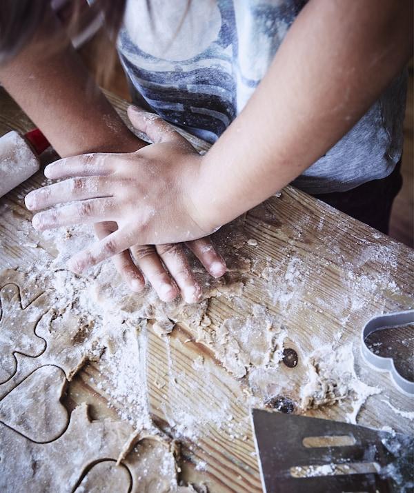 Gros plan d'un enfant découpant des formes dans la pâte sur un plan de travail enfariné.