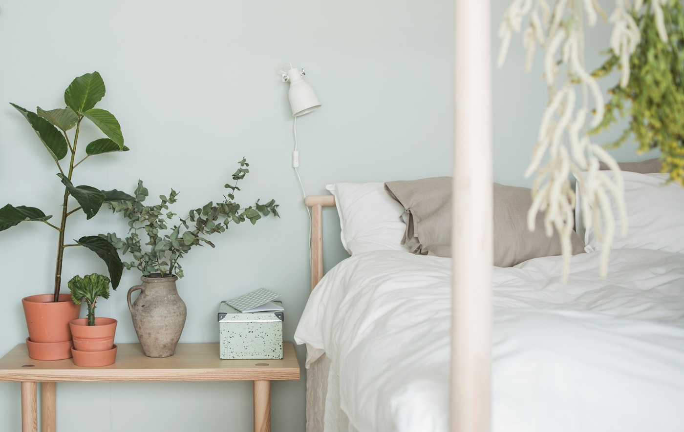 Gros plan d'un lit avec linge de lit naturel dans des tons pâles, sur fond de mur vert clair, avec table de chevet basse en frêne sur laquelle sont posées des plantes et une boîte de rangement