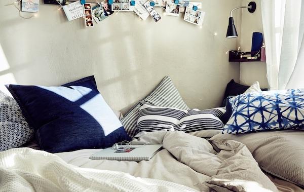 Gros plan d'un lit recouvert d'un linge de lit dans les tons neutres et de coussins bleus avec des motifs.