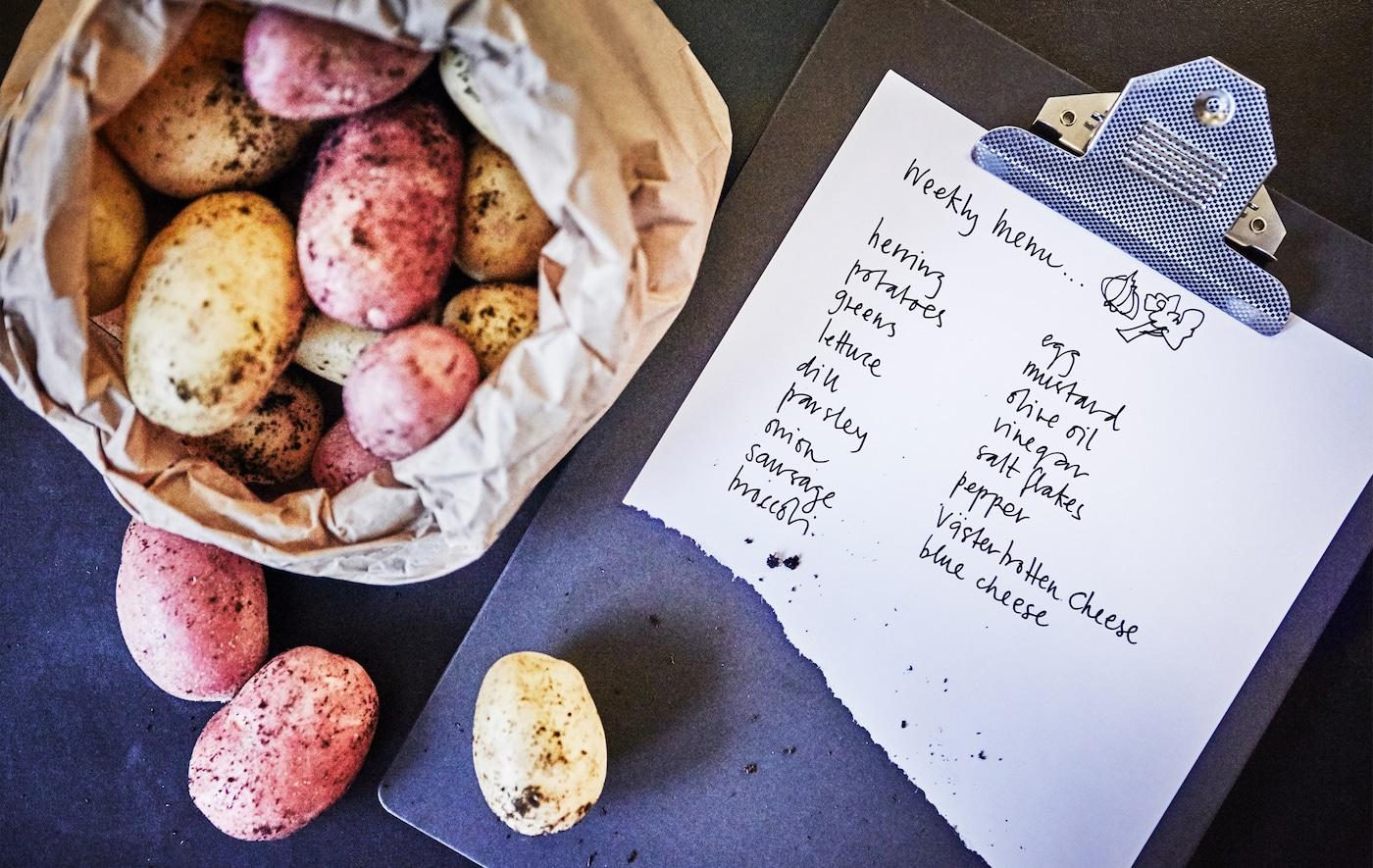 Gros plan d'un sac de pommes de terre et d'une liste de courses.