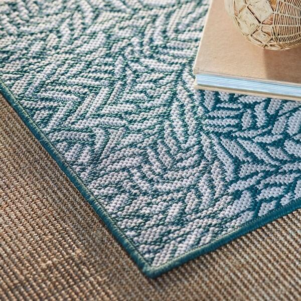 Gros plan d'un tapis à motifs de feuilles verts et beiges.