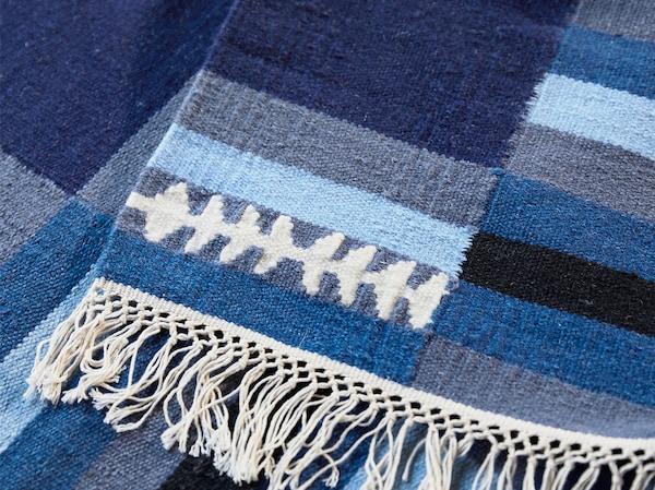 Gros plan d'un tapis en laine rayé TRANGET blanc, noir, gris et différents coloris bleus, fait à la main.
