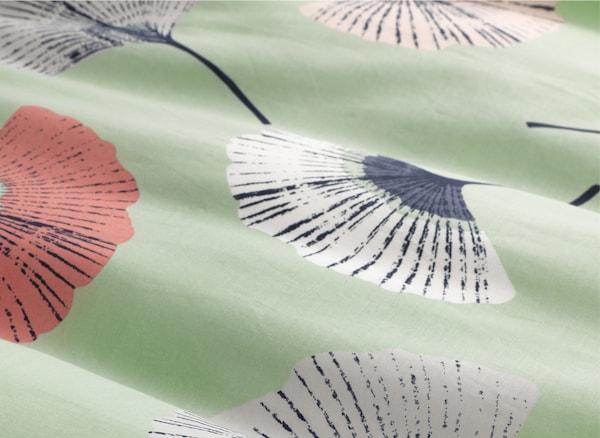 Gros plan d'un tissu vert pâle orné d'un motif floral.