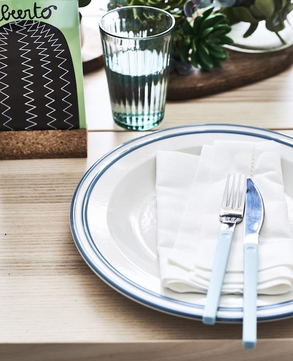 Gros plan d'une déco de table, avec assiette, serviette, couteau et fourchette.