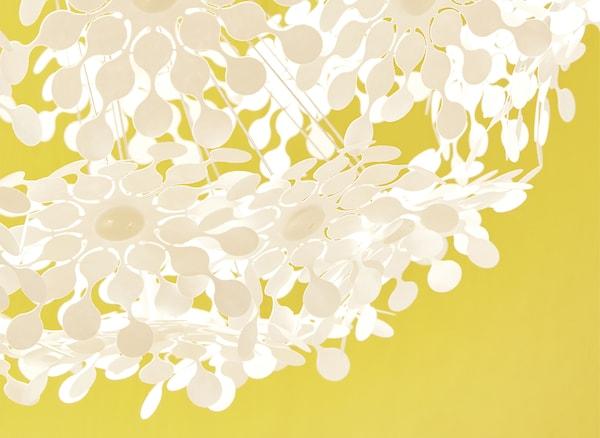 Gros plan d'une lampe décorée de fleurs blanches découpées, sur fond jaune.