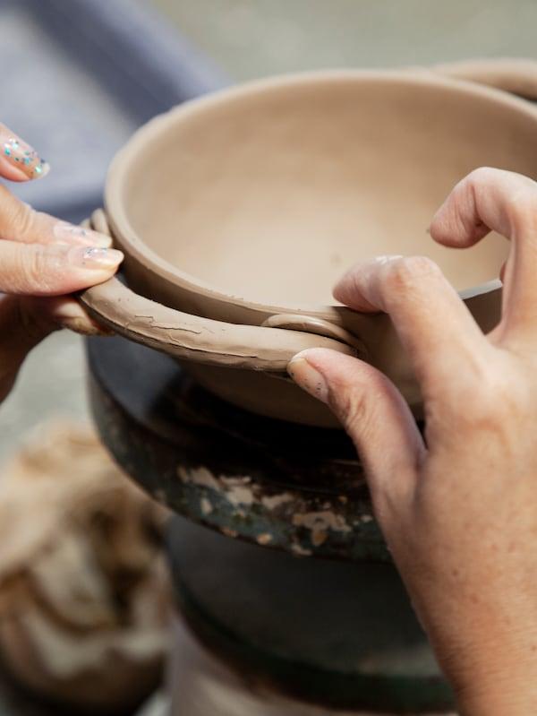 Gros plan montrant les mains d'une artisane en train d'appliquer une anse sur un bol en céramique fait main LOKALT.