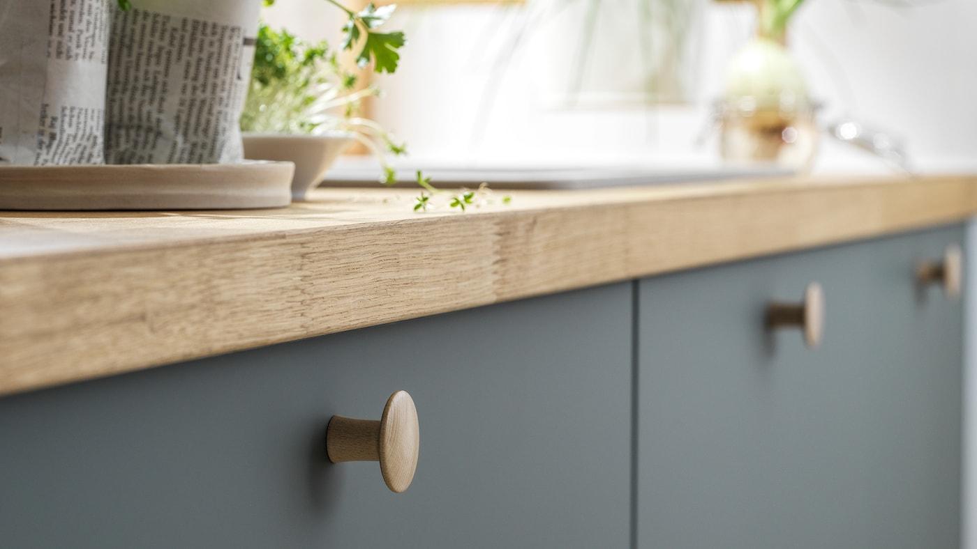 Gros plan sur des armoires de cuisine avec des façades de tiroirs BODARP au fini gris-vert et un comptoir en chêne plaqué avec des plantes vertes sur le dessus.