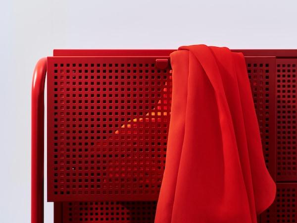Gros plan sur la commode NIKKEBY rouge de style industriel en métal ajouré.