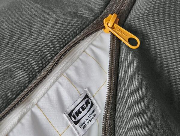Gros plan sur la fermeture à glissière verte du sac à dos DRÖMSÄCK et sur le tissu de l'intérieur.