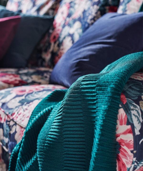 Gros plan sur le canapé UPPLAND, la housse à motif floral, des coussins bleus et un jeté sarcelle.