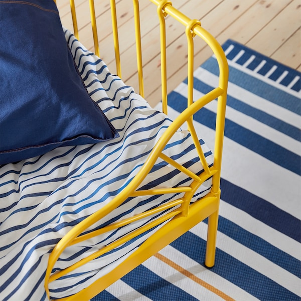 Gros plan sur le coin d'un lit jaune, le linge de lit blanc à rayures bleues et le tapis.
