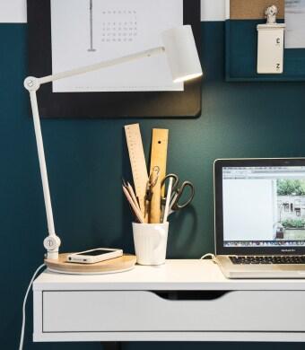 Gros plan sur le tiroir d'un bureau, un ordinateur portable et une lampe de travail dotée d'un chargeur sans fil.