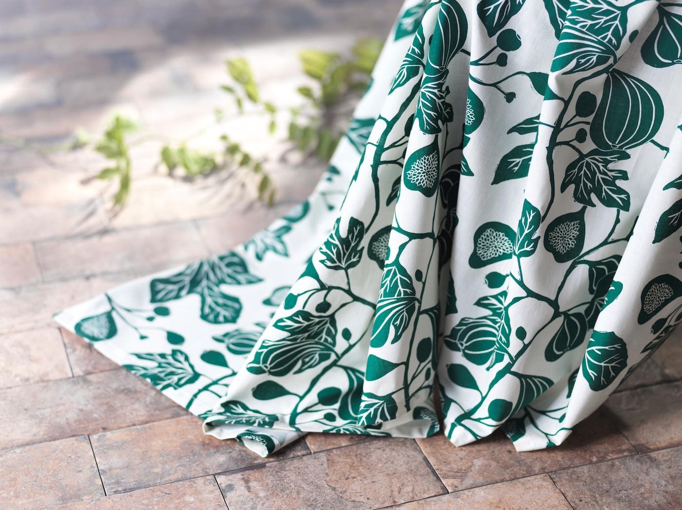 Gros plan sur les rideaux ALPKLÖVER qui touchent le sol et leur motif blanc et vert représentant des fleurs de figuier.