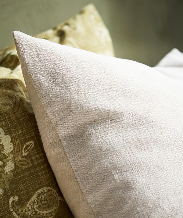 Gros plan sur un coussin beige en coton naturel à côté d'un coussin vert en cachemire.