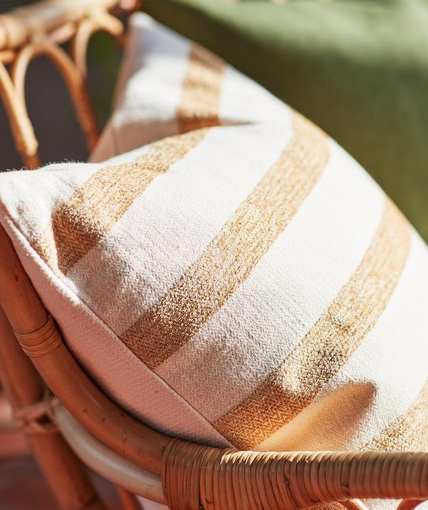 Gros-plan sur un coussin rayé en coton beige et brun clair sur une chaise en rotin.