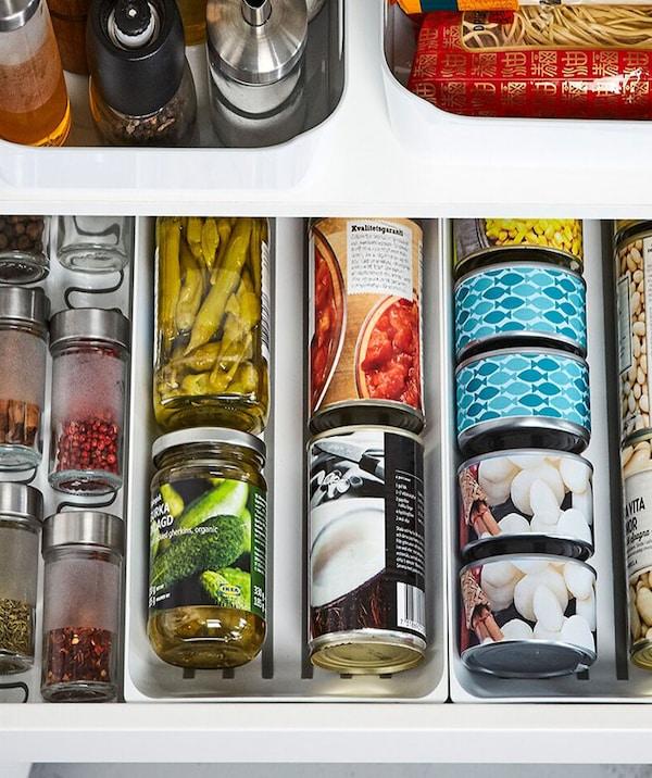 Gros plan sur un tiroir ouvert contenant des boîtes de conserve, des bocaux et des contenants à épices bien rangés grâce à des séparateurs pour tiroirs VARIERA.