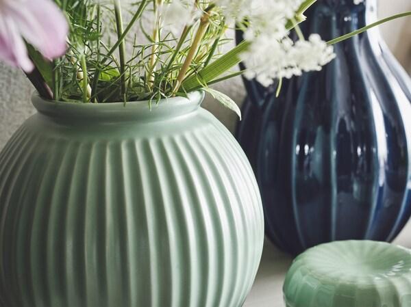 Gros plan sur un vase vert clair VANLIGEN avec des fleurs printanières et un vase/carafe VANLIGEN de couleur bleue à l'arrière plan.