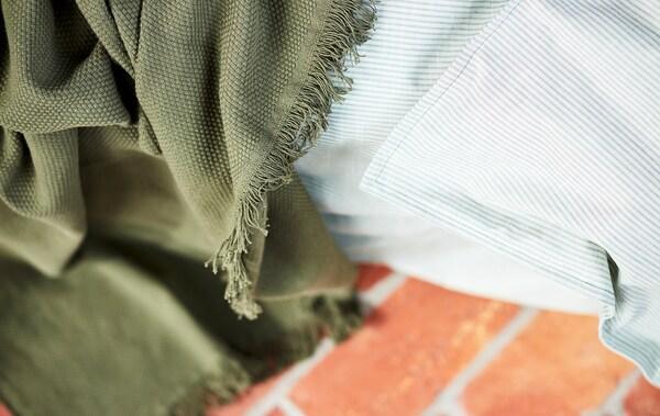 Gros-plan sur une couverture verte et un tissu rayé gris clair, posé sur un sol en pierre rouge.