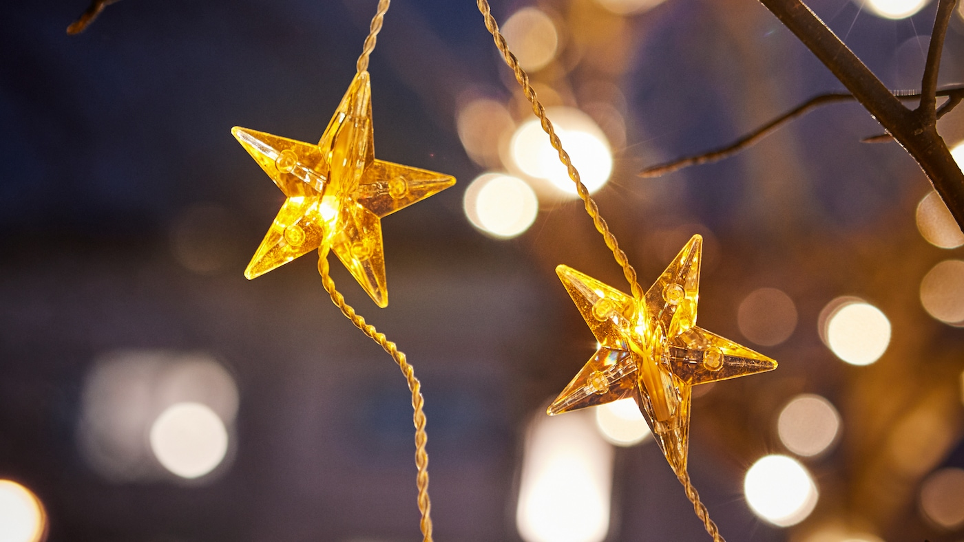 Gros plan sur une guirlande lumineuse à LED STRÅLA ornée d'étoiles dorées, accrochée à un arbre à l'extérieur.