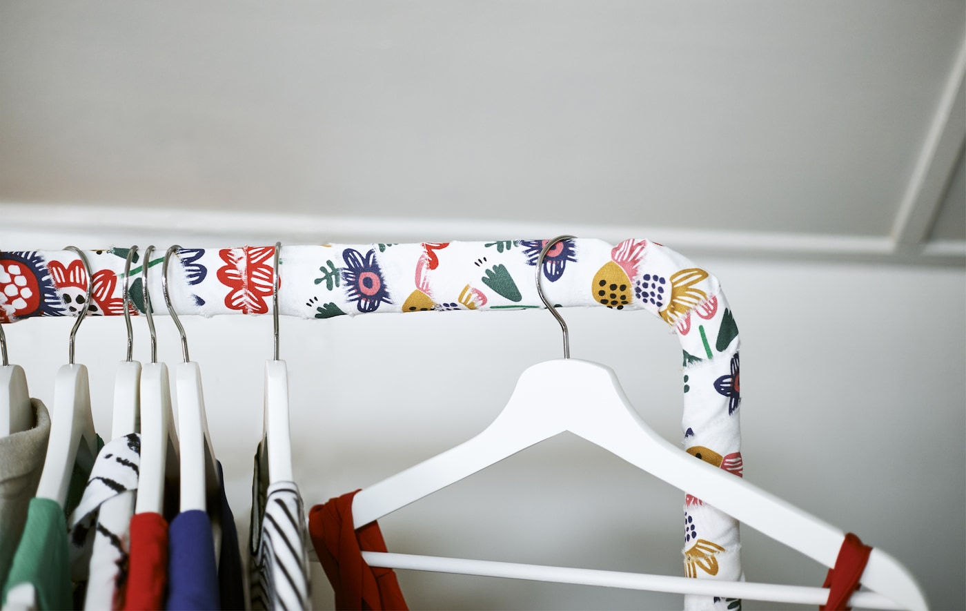 Gros plan sur une tringle à vêtements recouverte de tissu, avec des vêtements sur des cintres.