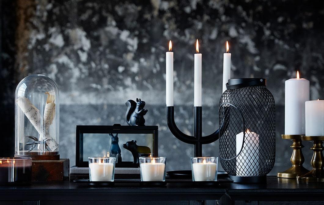 Gros plan sur une variété de bougies traditionnelles et à DEL placées sur une table de couleur foncée.