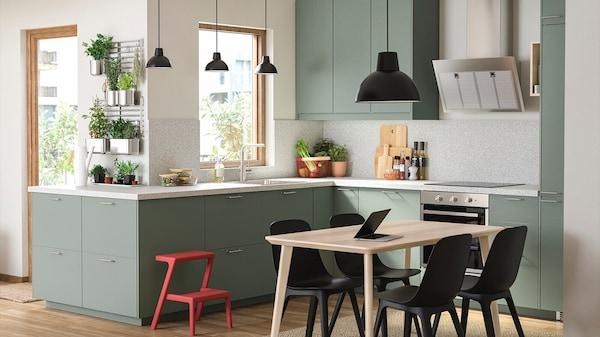 Große, offene Küche in grün mit Hängelampen, Esstisch aus Holz mit 4 schwarzen Stühlen sowie weitere Accessoires.