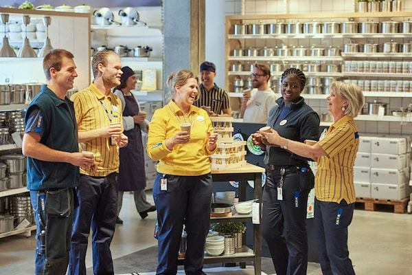 group of IKEA coworkers in IKEA uniforms standing in a group drinking coffee