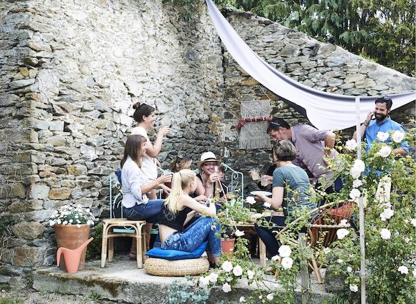 Groupe de personnes rassemblées prenant un verre sur la terrasse près du mur de pierre