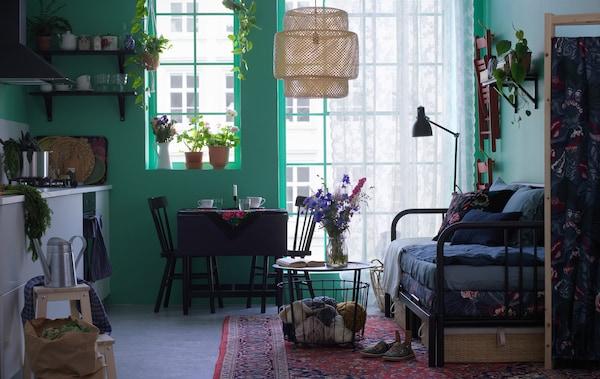 Grüner Wohn-& Essraum mit weißer Küchenzeile, Einkaufstüten, blumigem Tagesbett & schwarzem Esstisch