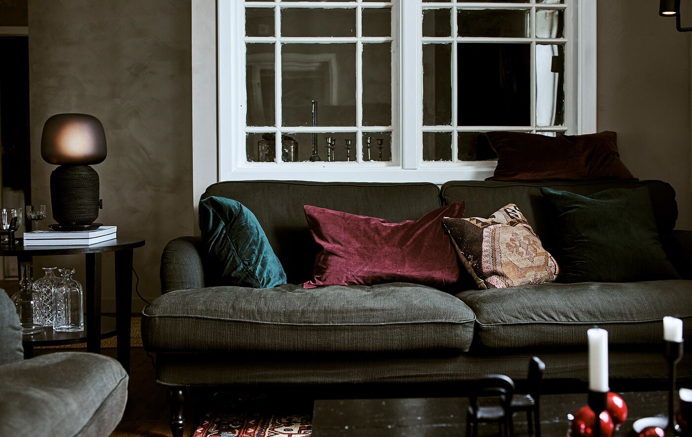 Grünes Sofa mit smaragdfarbenen Kissen in einem Wohnzimmer mit Fenster dahinter.