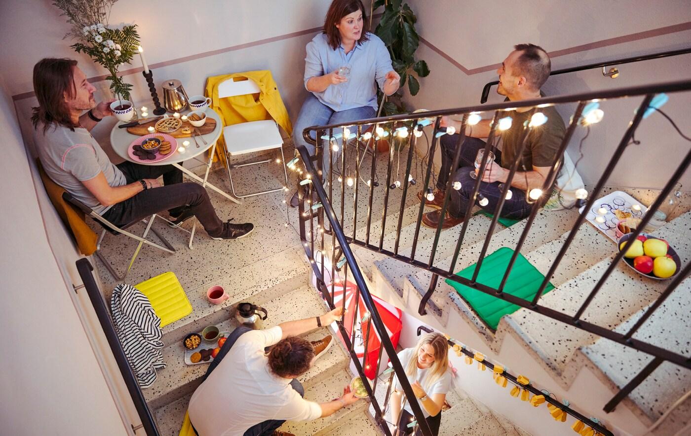 Grupa muškaraca i žena priča i deli grickalice dok sede na različitim nivoima stepeništa.