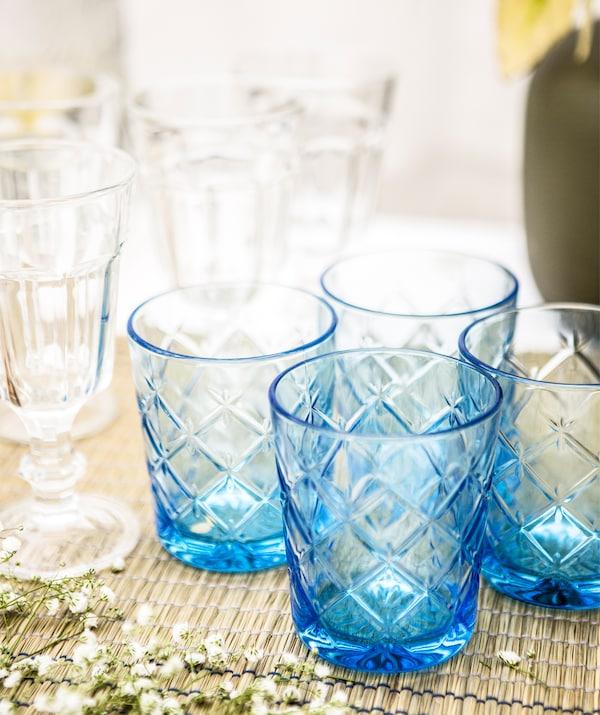 Grupa plavih čaša i prozirnih čaša za vino na nadstolnjaku.