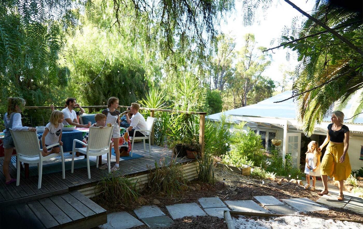 Grupo de personas sentadas alrededor de una mesa en una terraza elevada en un jardín con plantas y losetas.