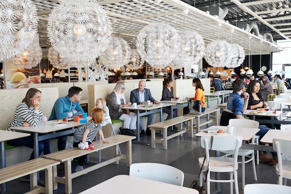 Grupos de familias sentadas en el restaurante de IKEA comiendo. Lamparas blancas en el techo que alumbran y mesas de madera con sillas blancas.