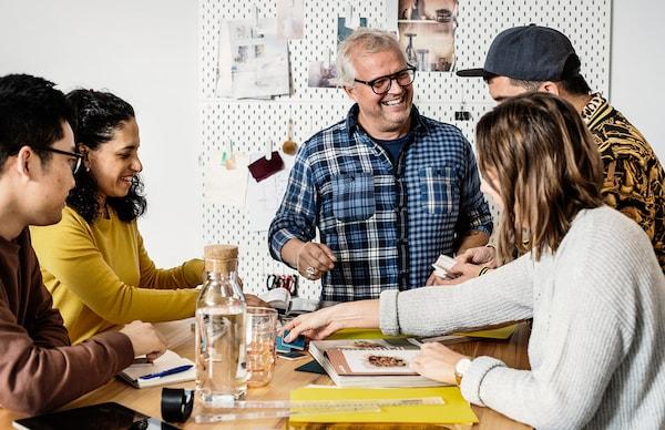 Gruppo di amici sorridenti intorno ad un tavolo - IKEA