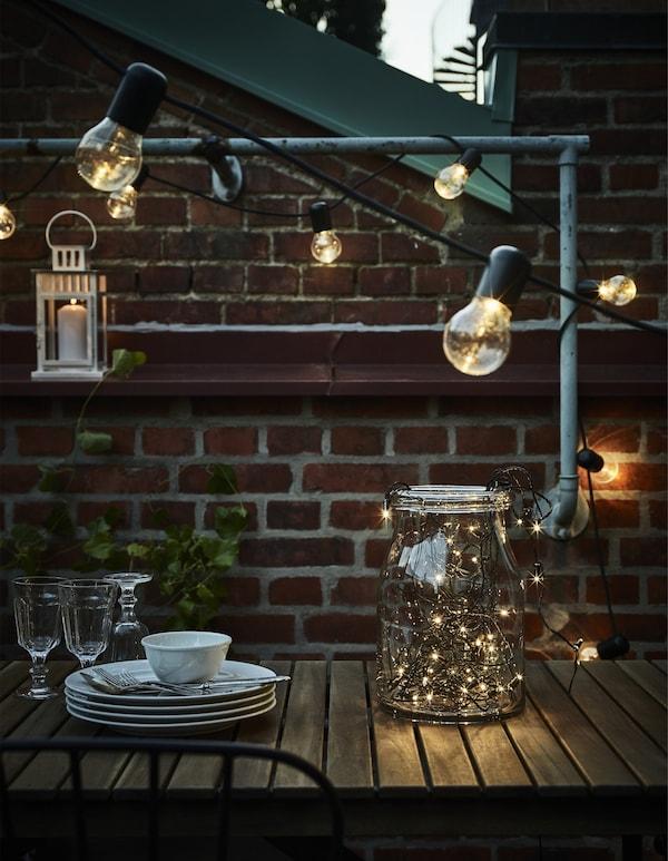 Guirlandas, un farolillo, algunos vasos y cubertería sobre una mesa en una terraza.