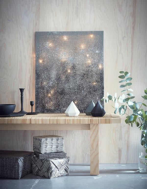 Guirnaldas luminosas colocadas detrás de un lienzo gris, apoyado en un banco de madera clara, con adornos y regalos.