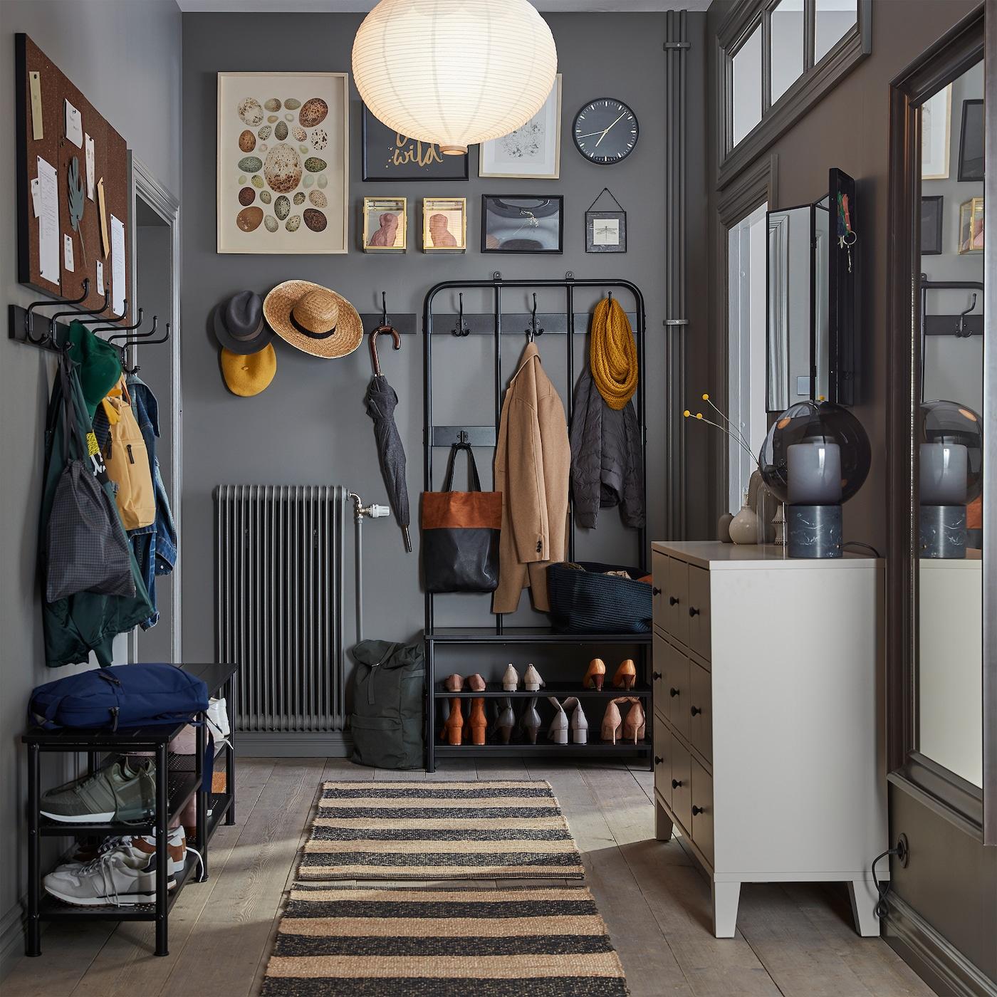 グレーでまとめられた狭めの玄関。ストライプのラグ、ベージュのチェスト、姿見、靴収納付きベンチ。